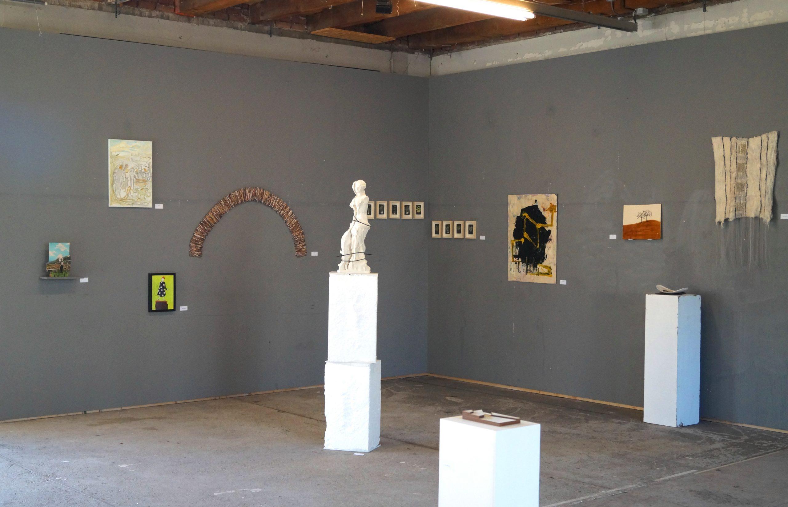 tentoonstelling met beelden en doeken aan muur