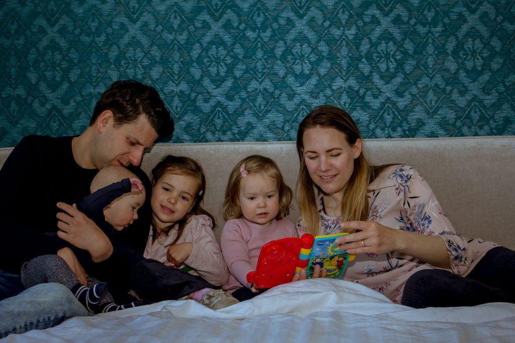 ouders met drie kinderen op bed